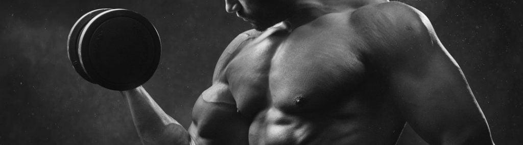 Muscular man curling a dumbbell