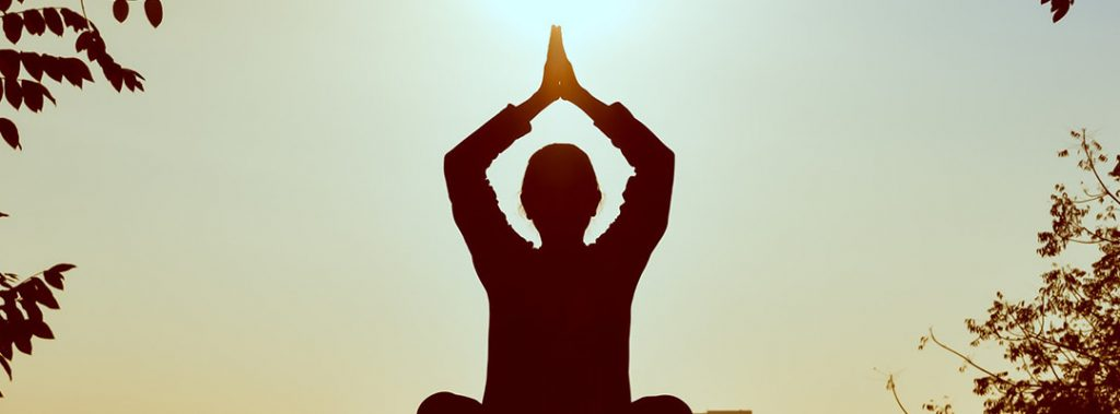 silhouette of a person meditating