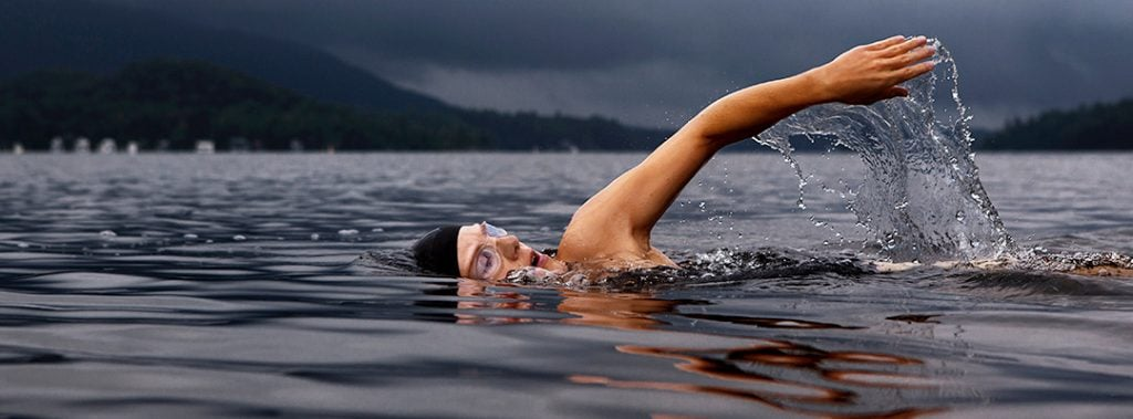 a woman has one arm out of the water while swimming